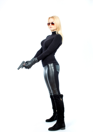 Young blonde woman in a black suit with a gun