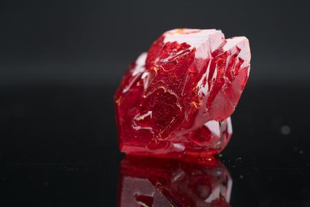黒い背景に赤い自然の結晶ミネラル