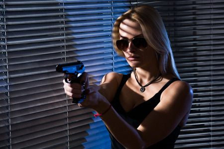 A young woman with a gun is standing by the window with blinds