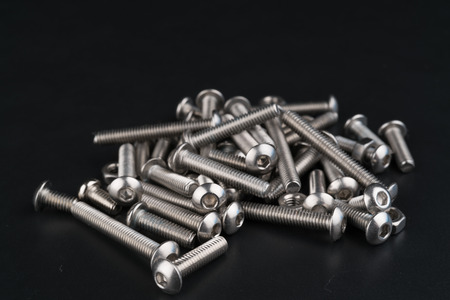 metal fasteners screws and nuts on black background. screw isolated on the black backgrounds. Nuts with bolts closeup Reklamní fotografie