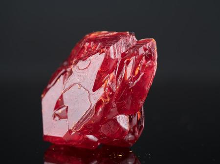 Rood natuurlijk kristalmineraal op een zwarte achtergrond