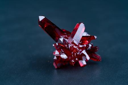 自然起源の赤い結晶。黒の背景にルビー色の結晶のクローズアップ 写真素材