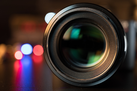 The photo or videocamera lens on dark background with lense reflections Imagens