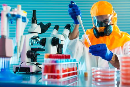 Ricerca di virus pericolosi in laboratorio. Prevenzione di una pandemia. Uno scienziato in una tuta protettiva biologica lavora con una pipetta Archivio Fotografico