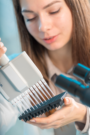 Student woman with multi pipette and other PCR items in microbiological  genetic laboratory Stock Photo