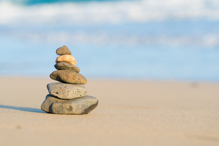 pyramid of stones on a sandy beach on the sea