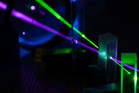 green and blue laser on optical table in physics laboratory