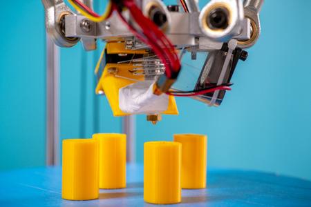 Print orange parts on a 3D printer in printing process Фото со стока