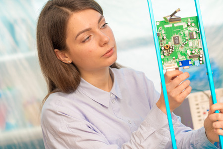 Female student in electronics class uses a Measuring device