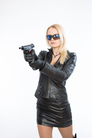 Young woman in sunglasses and a gun