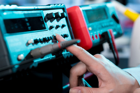 Engineer hand use Electrical equipment (Insulation tester) for measure i circuit.