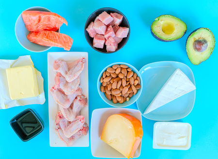 Ketogenic diet food. Low-carb food background, fish, meat, cheese, nuts, oil and butter on a blue background. mockup,  flatlay, flat lay Top view Keto diet concept. 版權商用圖片