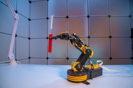 Test tube in robot arm. robot manipulates chemical tubes in the laboratory