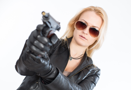 Beautiful young blond woman wearing sunglasses holding a gun Banque d'images