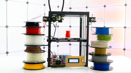 3d printer and plastic filament on color background Imagens