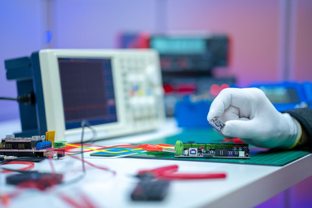 Development of electronic devices in the modern electronics laboratory, on a table, microprocessor oscilloscope and multimeter