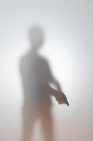 blurred silhouette of a man with a gun Imagens