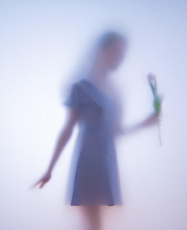 Blurred photo girl with flowers behind glass Imagens