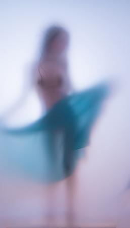 Fille photo floue avec un chiffon dansant derrière une vitre