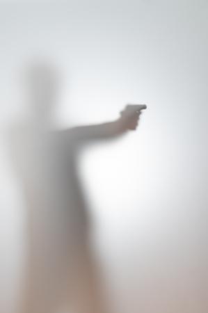 sagoma sfocata di un uomo con una pistola