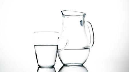 jar and glass of water on white background