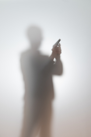 blurred silhouette of a man with a gun 写真素材