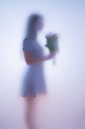 Blurred photo girl with flowers behind glass