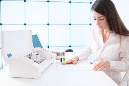 Young woman in printing office insert paper and color pens on plotter Stock Photo