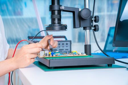 Woman worker in laboratory of electronics devices