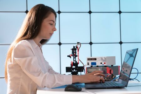 A young woman writes an algorithm for the robot arm. Science Research Laboratory for Robotic Arm Model. Computer Laboratory Stok Fotoğraf
