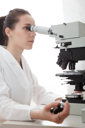 Laboratory assistant uses a polarizing microscope in a microbiological laboratory