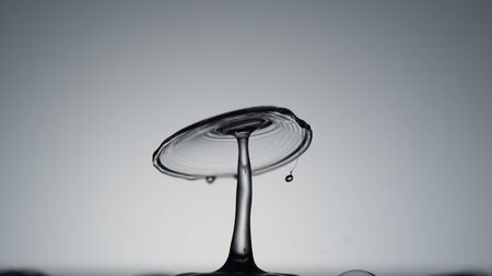 Close-up of a water drop falling on water surface Stockfoto