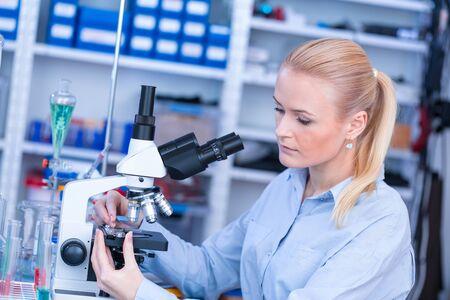 Mädchen mit Objektträger für das Mikroskop Universitätsklinikum. Attraktiver junger Wissenschaftler mit Blick auf den Objektträger im forensischen Labor Standard-Bild
