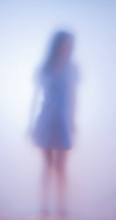 Blurred photo girl wearing dress dancing behind glass