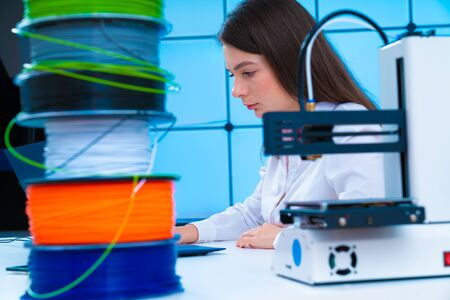 Young woman in design office with 3d printer and plastic filament printing concept model Stock Photo