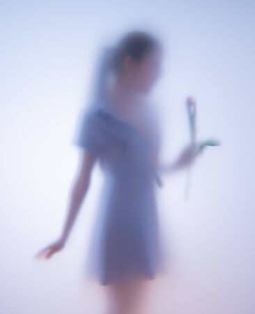 Blurred photo girl with flowers behind glass Stok Fotoğraf