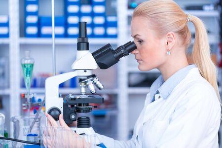 Dziewczyna ze szkiełkiem do mikroskopu Szpital Uniwersytecki. Atrakcyjny młody naukowiec patrzący na szkiełko mikroskopowe w laboratorium kryminalistycznym
