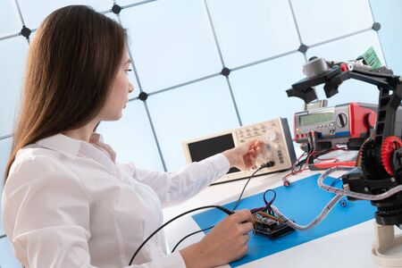 A young woman writes an algorithm for the robot arm. Science Research Laboratory for Robotic Arm Model. Computer Laboratory Zdjęcie Seryjne