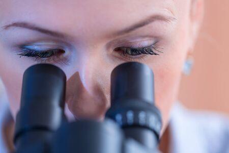 Meisje met een dia voor de microscoop Universitair Ziekenhuis. Aantrekkelijke jonge wetenschapper die naar het microscoopglaasje kijkt in het forensisch laboratorium