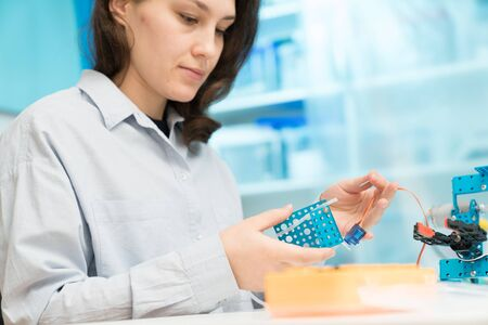 Student woman in robotics laboratory working  on project mechatronics