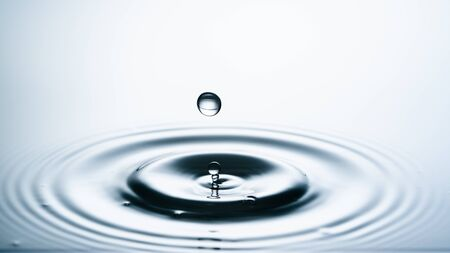 Close-up of a water drop falling on water surface