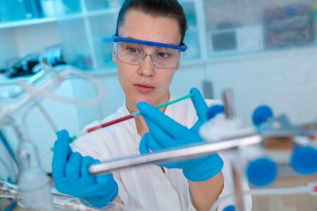 Young woman in chemical lab Young woman in chemical lab. cience professional pipetting solution into the glass cuvette.
