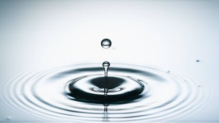Close-up of a water drop falling on water surface Banco de Imagens