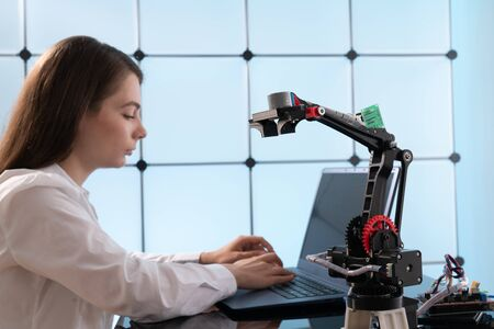 A young woman writes an algorithm for the robot arm. Science Research Laboratory for Robotic Arm Model. Computer Laboratory Stock Photo