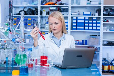 Girl laboratory Assistantworks with an antiviral drug in a pharmaceutical laboratory