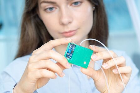 Young scientist woman in microbiological lab with lab-on-chip LOC microfluidic device
