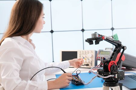 Woman student with robot model arm in university laboratory