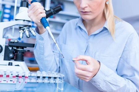 Girl laboratory Assistant works with an antiviral drug in a pharmaceutical laboratory