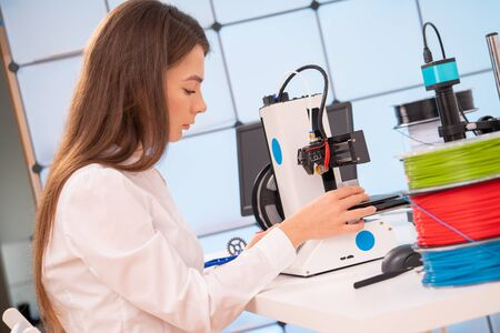 Young female designer working on a prototype device on a 3D printer Stock fotó