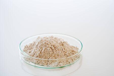 Calcium carbonate salt in petri dish on white background